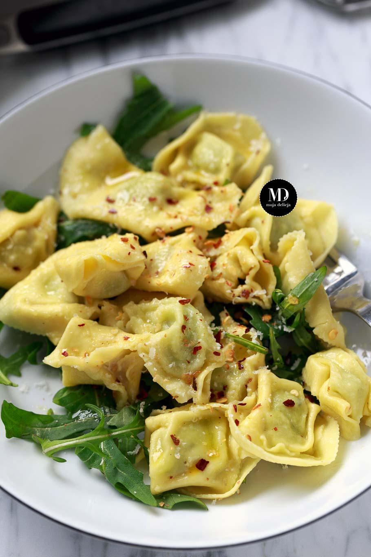 Tortellini z ricottą i szpinakiem na rukoli z oliwą i parmezanem